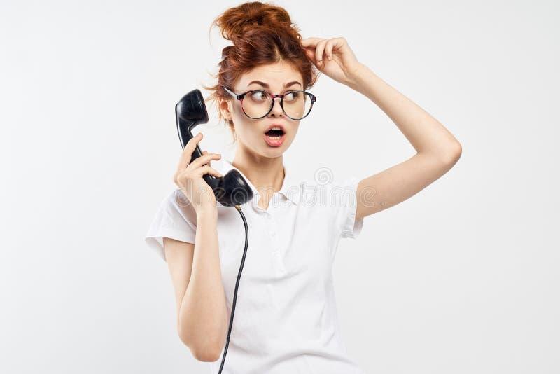 De vrouw op een lichte achtergrond houdt een telefoon in glazen, emoties, mededeling stock foto's