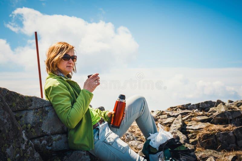 De vrouw op middelbare leeftijd heeft een rust met een kop van warme koffie stock foto's