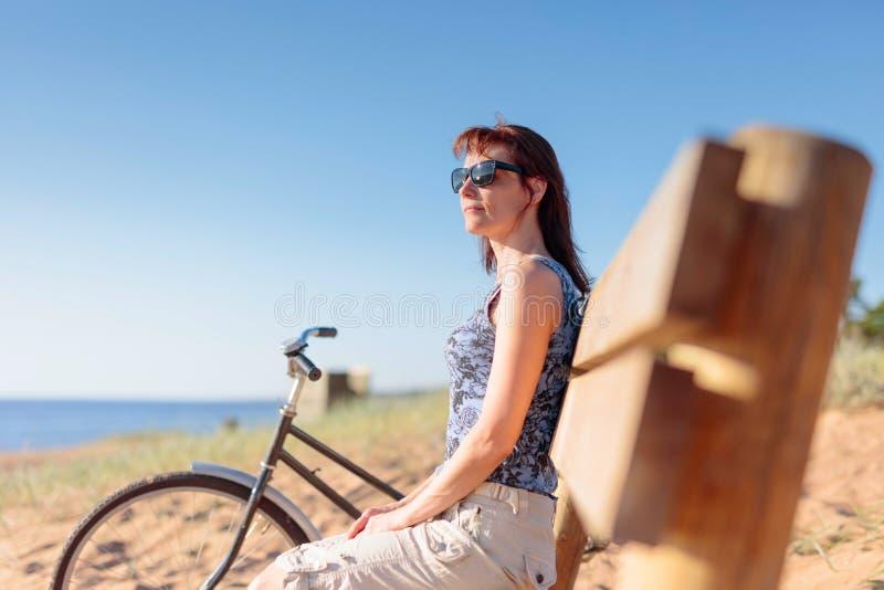 De vrouw op middelbare leeftijd kwam op een Fiets aan het strand en rustende zitting op een bank royalty-vrije stock foto's