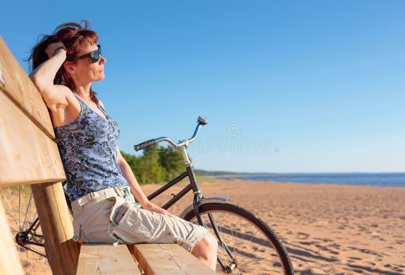 De vrouw op middelbare leeftijd kwam op een Fiets aan het strand en rustende zitting op een bank royalty-vrije stock afbeeldingen
