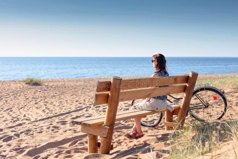 De vrouw op middelbare leeftijd kwam op een Fiets aan het strand en rustende zitting op een bank royalty-vrije stock afbeelding