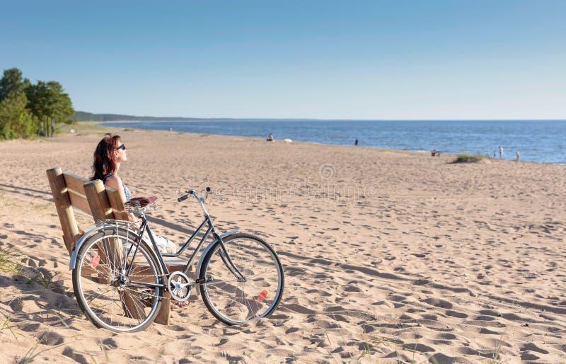 De vrouw op middelbare leeftijd kwam op een Fiets aan het strand en rustende zitting op een bank stock afbeeldingen