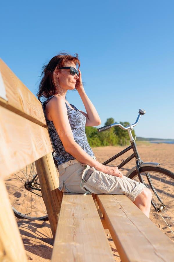 De vrouw op middelbare leeftijd kwam op een Fiets aan het strand en rustende zitting op een bank stock foto