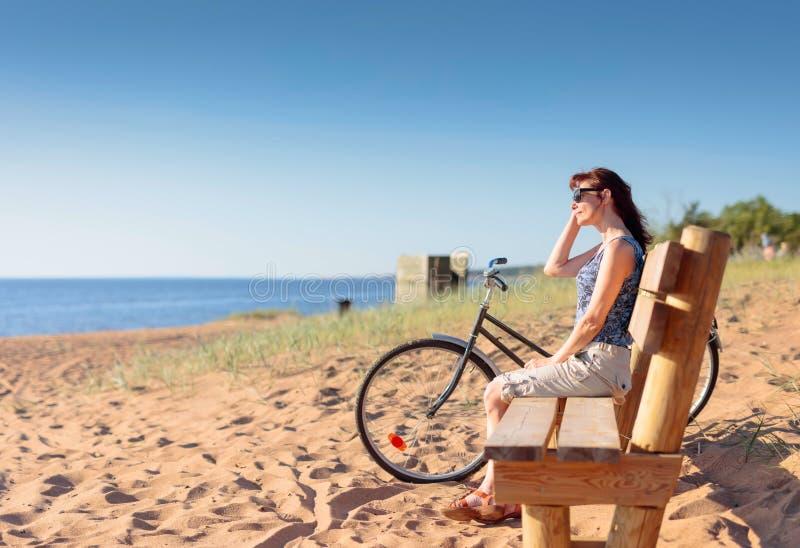De vrouw op middelbare leeftijd kwam op een Fiets aan het strand en rustende zitting op een bank stock afbeelding