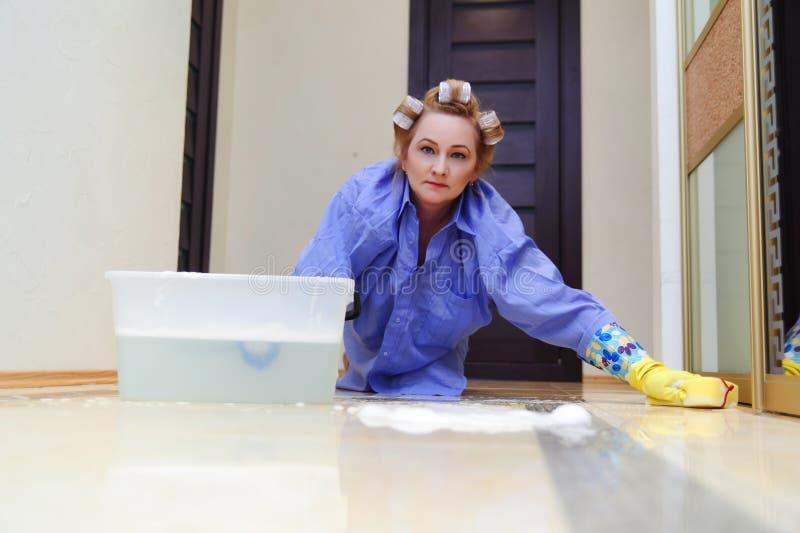 De vrouw op middelbare leeftijd wast de vloeren royalty-vrije stock afbeeldingen