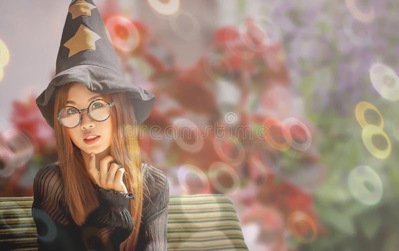 De vrouw op zwarte kleding kijkt als mooie heks zit in tuin stock foto
