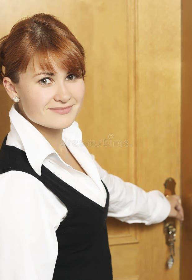 De vrouw opent een deur stock afbeelding