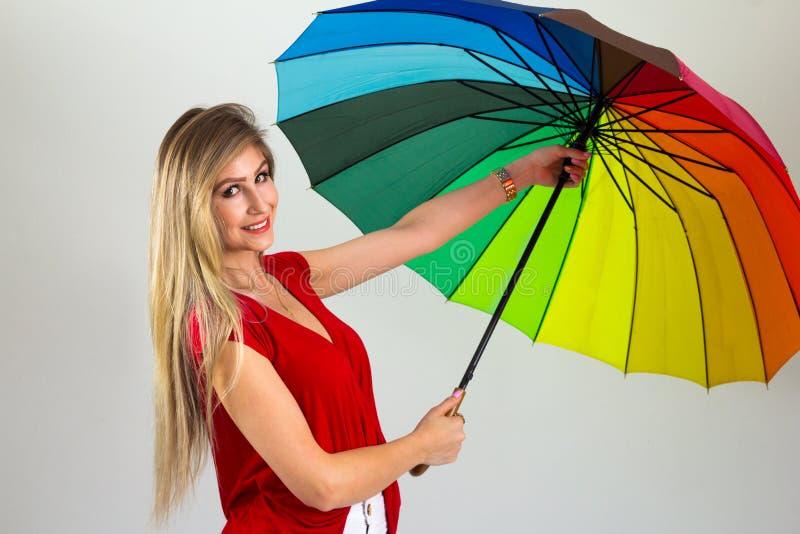 De vrouw opent een kleurrijke paraplu Blonde persoon en het dragen royalty-vrije stock afbeeldingen