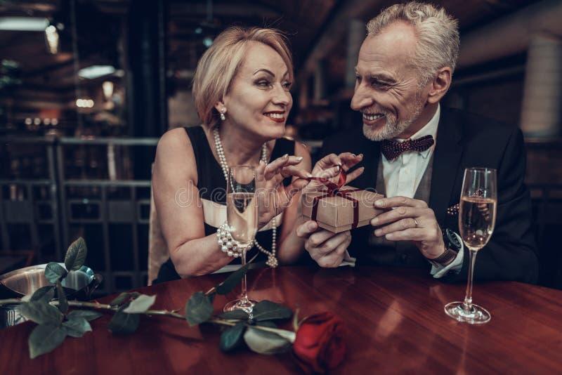 De vrouw opent gift met de haar Mens in Restaurant stock foto