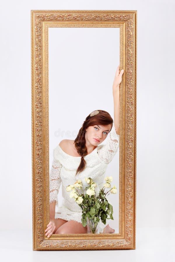 De vrouw in openwork kleding zit op vloer achter groot frame royalty-vrije stock afbeeldingen