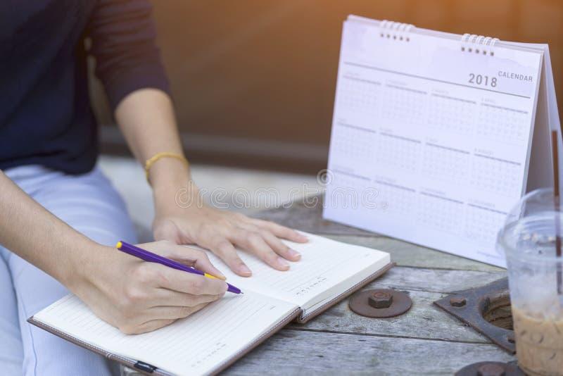 De vrouw overhandigt het schrijven plan op notitieboekje, planningsagenda en programma gebruikend de ontwerper van de kalendergeb royalty-vrije stock afbeelding