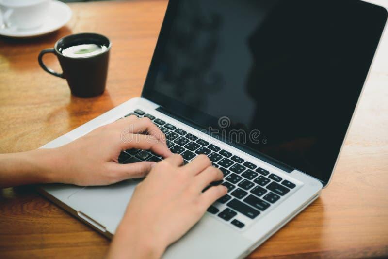 De vrouw overhandigt het typen laptop computer met het lege scherm op lijst in koffiewinkel stock afbeelding