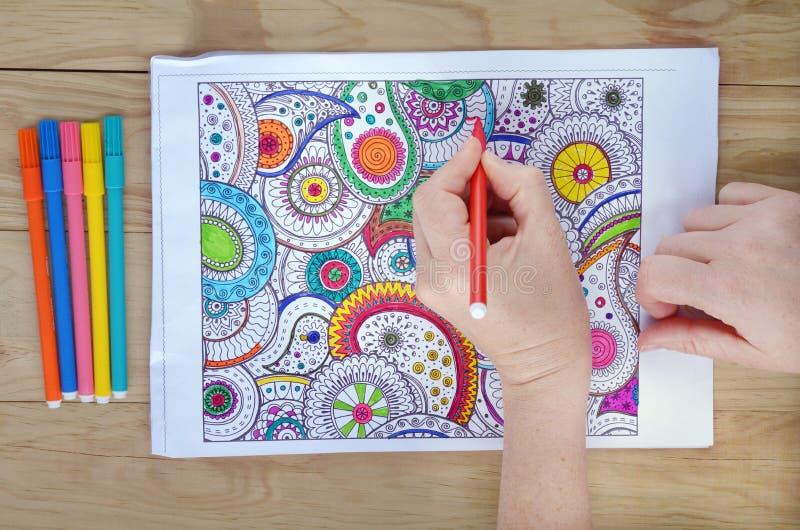 De vrouw overhandigt kleurende patronen op een kleurende pagina voor spanning rel royalty-vrije stock fotografie