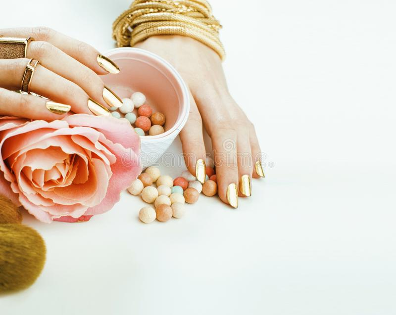De vrouw overhandigt met gouden manicure vele ringen die borstels houden, omhoog kunstenaarsmateriaal modieus en zuiver maken stock afbeelding