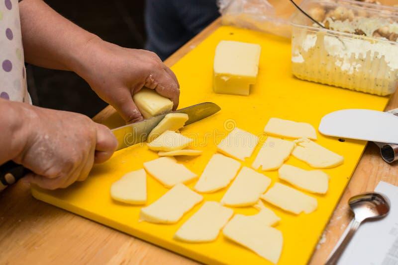 De vrouw overhandigt plakkenkaas om een Italiaanse pizza, proces van p te maken royalty-vrije stock afbeelding