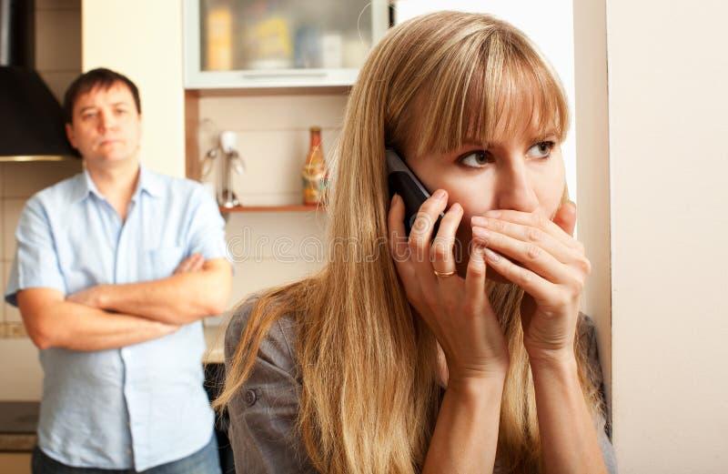 De vrouw overlegt persoonlijk de telefoon stock foto