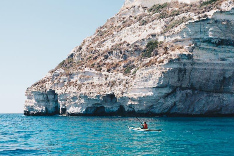 De vrouw paddelt kajak in een kalme overzees in Sardinige Italië stock afbeelding