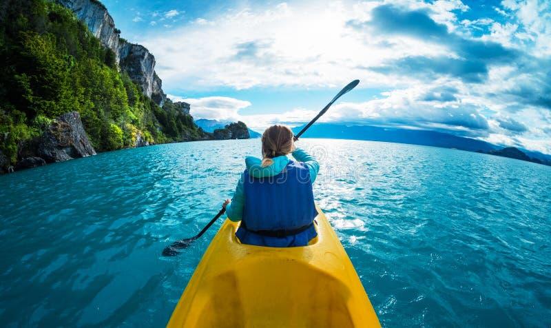 De vrouw paddelt kajak in het meer met turkoois water royalty-vrije stock afbeelding