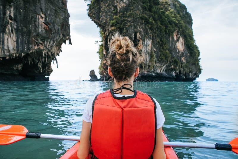 De vrouw paddelt kajak in het meer met turkoois water royalty-vrije stock fotografie