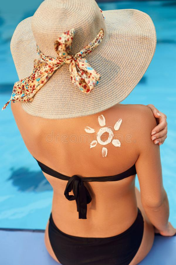 De vrouw past de bescherming van de zonroom op gelooide schouder toe Schoonheids skincare zon het verouderen beschermingslichaams stock foto's