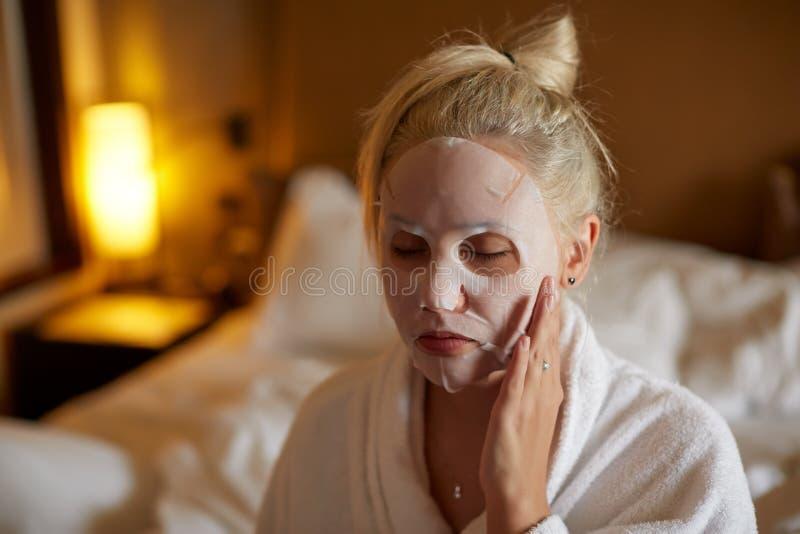 De vrouw past bladmasker op haar gezicht in de slaapkamer toe royalty-vrije stock foto's
