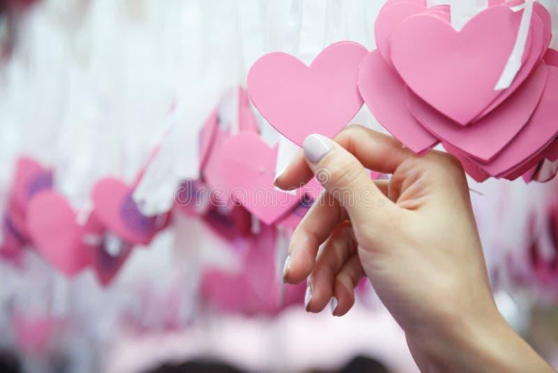 De vrouw plukt roze die hartvorm Lucky Draw aan wit lint bij het wensen van boom in liefdadigheidsgebeurtenis wordt verbonden met stock foto