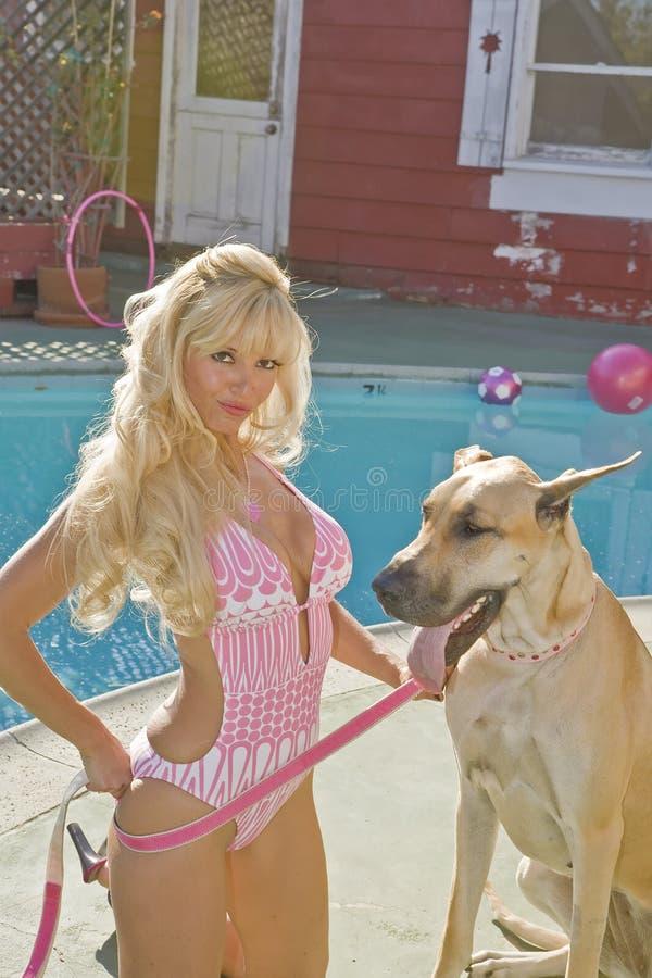 De Vrouw Poolside van de blonde met een Groot Deen stock foto