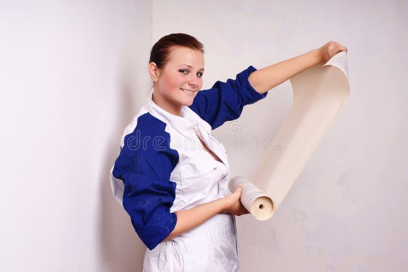 De Vrouw Probeert Op Behang Aan Muur Royalty-vrije Stock Foto's