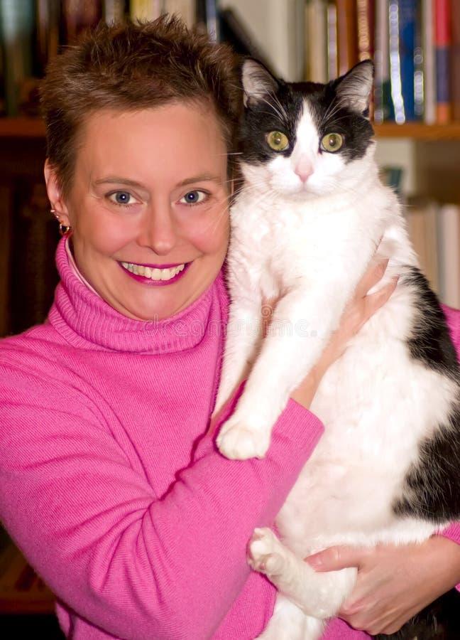 De vrouw pronkt met haar huisdierenkat stock fotografie