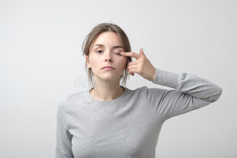 De vrouw raakt haar oog om aan te tonen dat zij probleem met zicht heeft Gezondheidsprobleem stock afbeeldingen