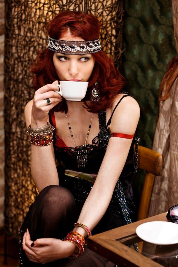De vrouw in retro kleren drinkt koffie in koffiestaaf royalty-vrije stock fotografie