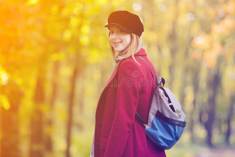 De vrouw in rode laag en de rugzak hebben een rust in autumpark stock foto
