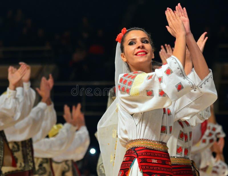 De vrouw in Roemeense traditionele uitrusting presteert tijdens de dancesportconcurrentie