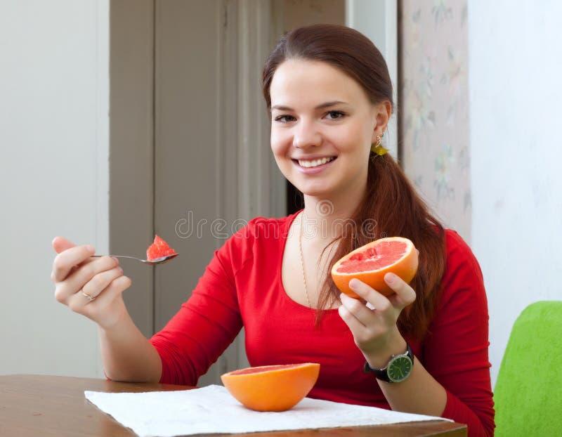 De vrouw in rood eet thuis grapefruit stock afbeelding