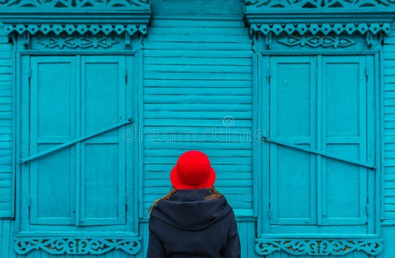 De vrouw in rood GLB bekijkt het blauwe oude dorpshuis in een Russisch dorp royalty-vrije stock afbeeldingen