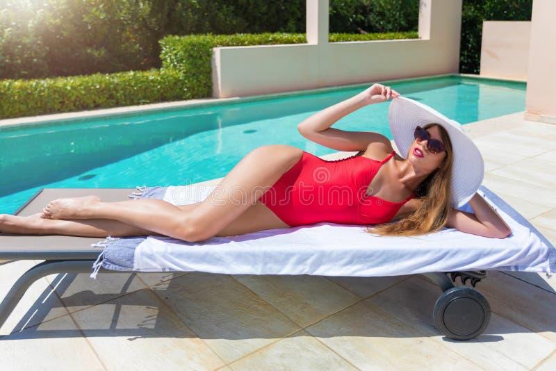 De vrouw in rood zwempak en witte sunhat ontspant door de pool stock fotografie