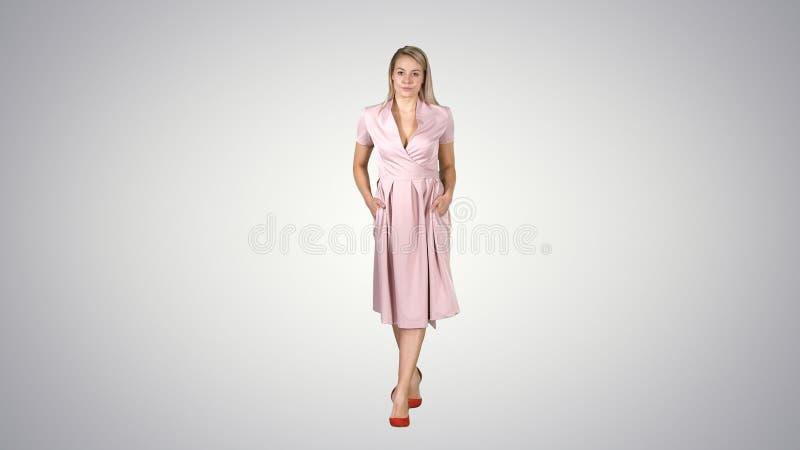 De vrouw in roze kleding met dient zakken in loopt naar de camera op gradiëntachtergrond royalty-vrije stock foto's