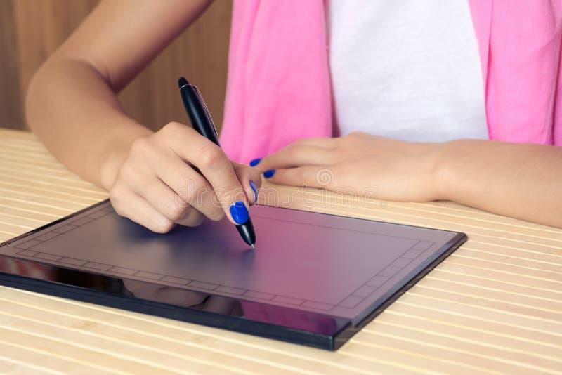 De vrouw in roze sjaal en blauwe manicure trekt op de tablet bij een houten lijst royalty-vrije stock afbeelding