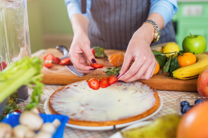 De vrouw s overhandigt het zetten van gesneden aardbei op cake Huisvrouw die fruit en bessendessert maken stock foto