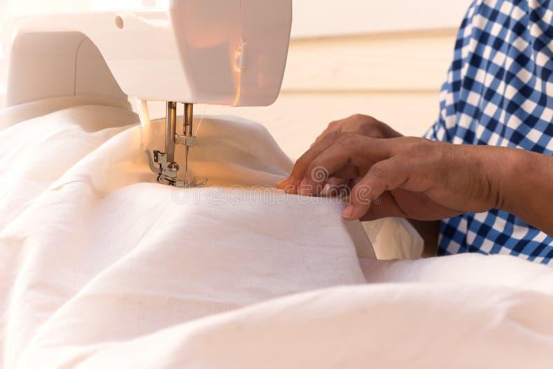 De vrouw ` s overhandigt naaiend linnenkatoen met naaimachine stock fotografie