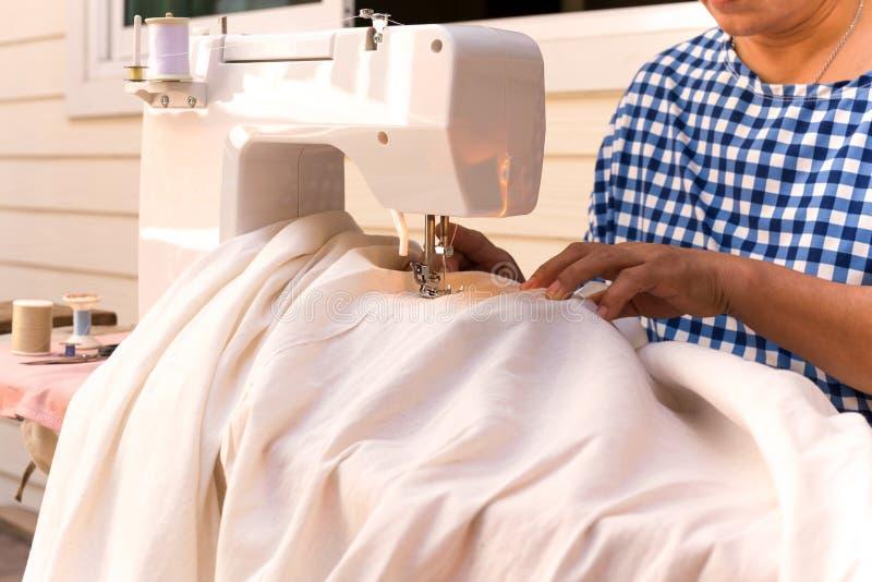 De vrouw ` s overhandigt naaiend linnenkatoen met naaimachine stock afbeelding