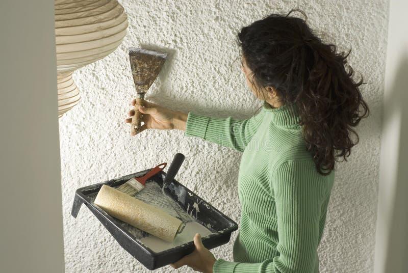 De vrouw schaaft Muur terwijl Horizontaal Schilderen - stock foto's