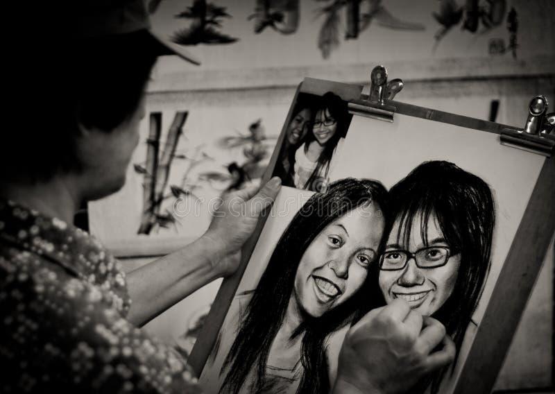 De vrouw schetst een paar vrouwelijke gezichten van een foto royalty-vrije stock afbeeldingen