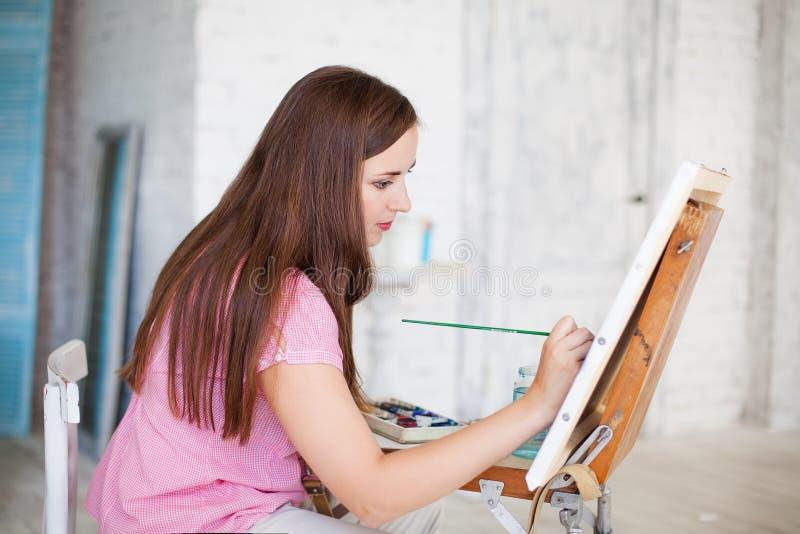 De vrouw schildert beeld op canvas royalty-vrije stock afbeeldingen