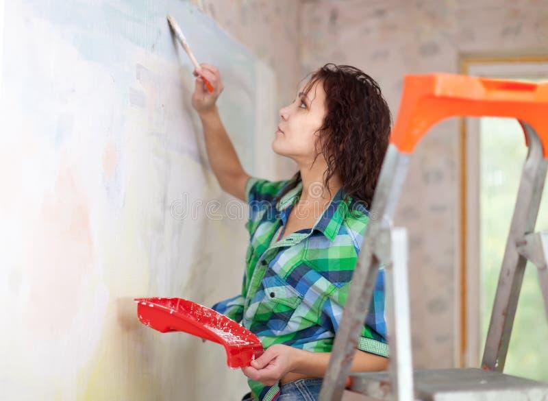 De vrouw schildert thuis muur stock afbeelding