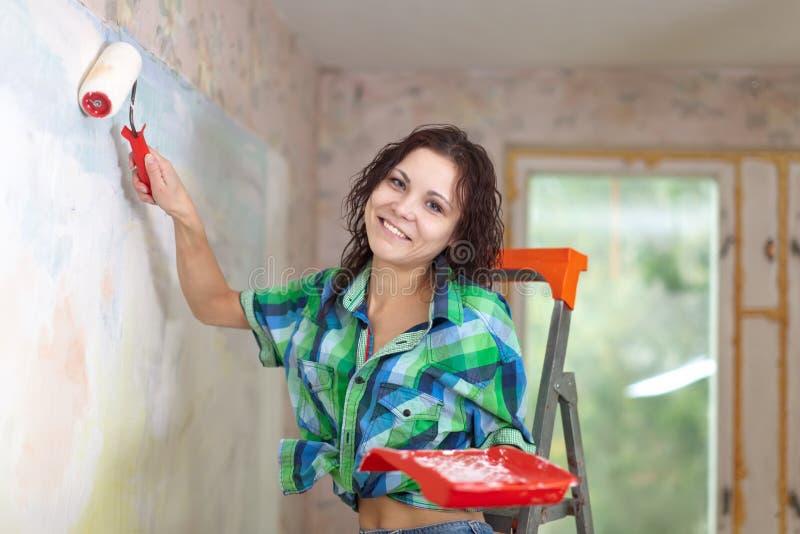De vrouw schildert thuis muur royalty-vrije stock foto