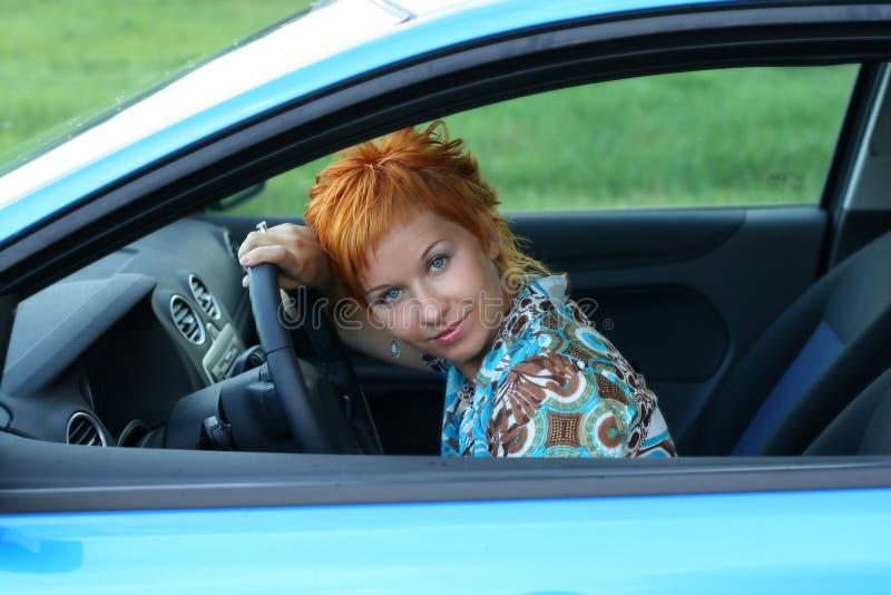 De vrouw situeert in een auto stock fotografie