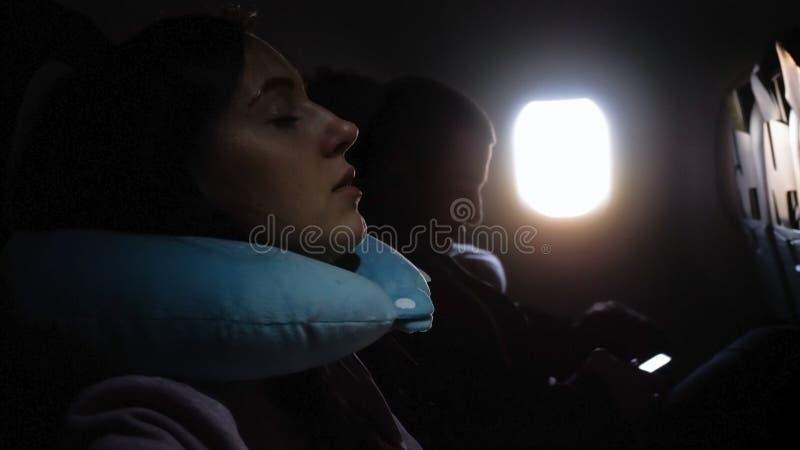 De vrouw slaapt in een vliegtuig stock afbeeldingen