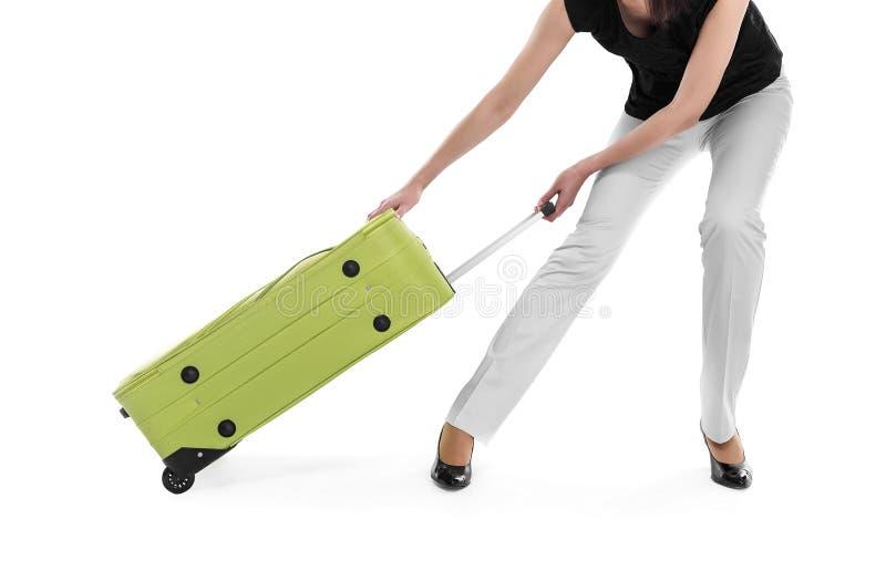De vrouw sleept een zware koffer royalty-vrije stock afbeelding