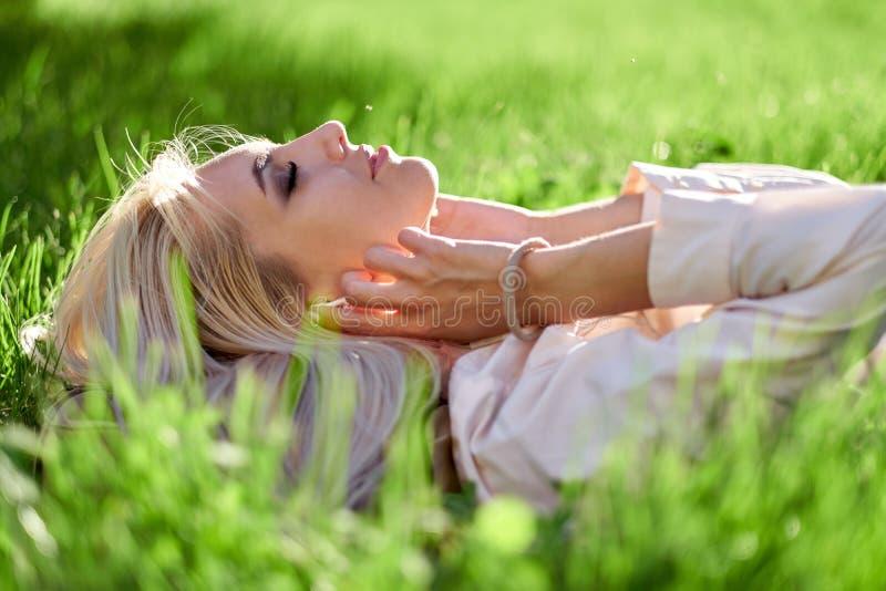 De vrouw sloot haar ogen en het luisteren muziek met haar hoofdtelefoons en het liggen in weide Geniet van muziek, ontspant royalty-vrije stock foto's